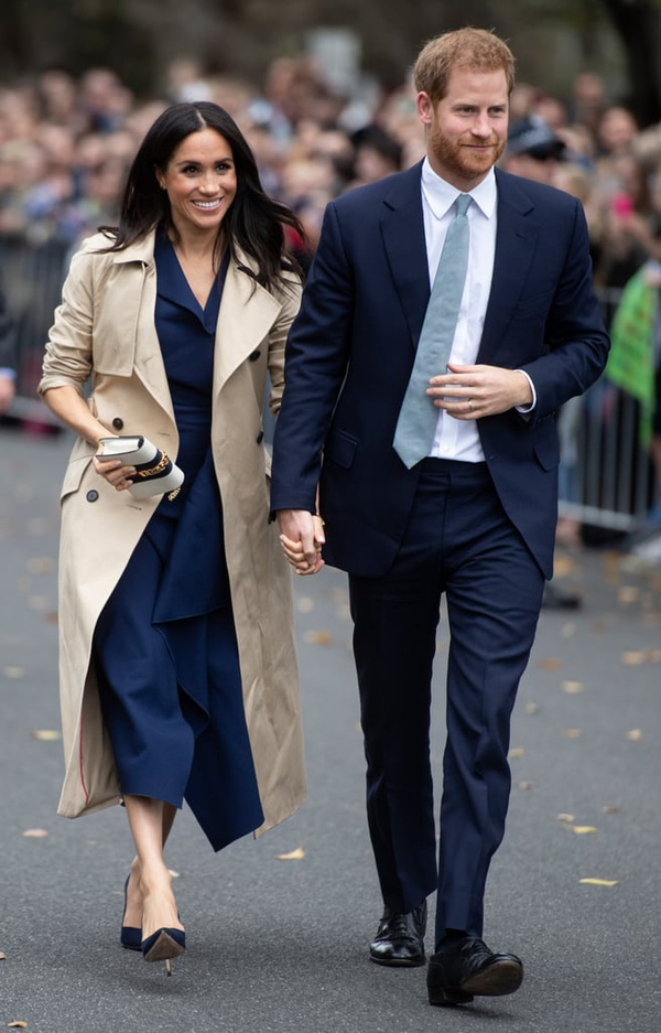 Martin Grant - PRINCE HARRY AND MEGHAN, THE DUCHESS OF SUSSEX IN MELBOURNE, AUSTRALIA. MEGHAN IS WEARING MARTIN GRANT BEIGE TRENCH COAT FROM RESORT SS19 COLLECTION.